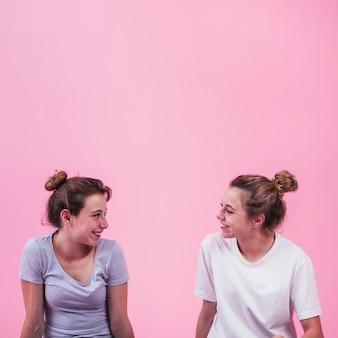 Dois, sorrindo, mulheres jovens, olhando um ao outro, contra, fundo cor-de-rosa