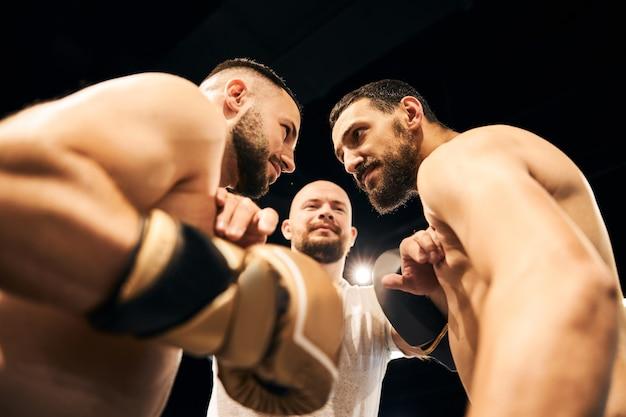 Dois sparrings olhando violentamente um para o outro enquanto o árbitro os mantinha separados