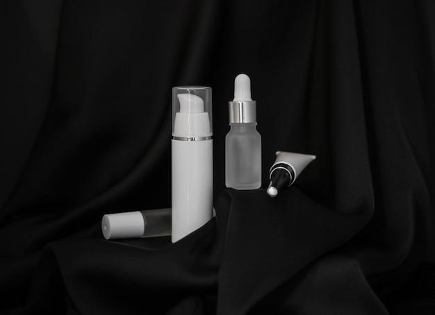 Dois sprays cosméticos, um pequeno grande, um frasco com uma pipeta e um tubo de cosmético estão em um fundo preto