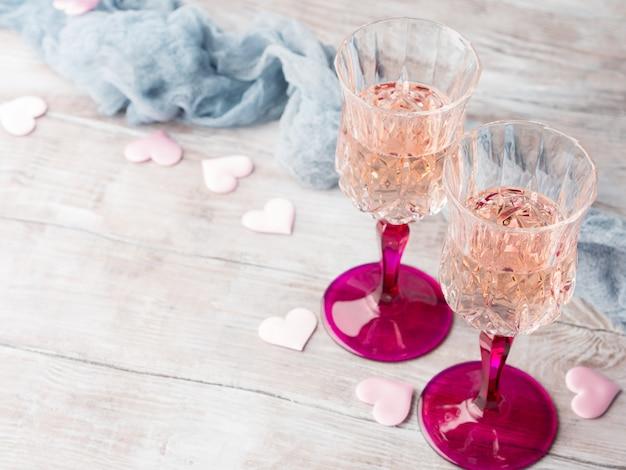 Dois stemmed vidros do champanhe com corações cor-de-rosa em de madeira textured. convite de data romântica de casamento de dia dos namorados