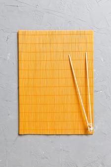 Dois sticks de treinamento de sushi com esteira de bambu vazia ou placa de madeira