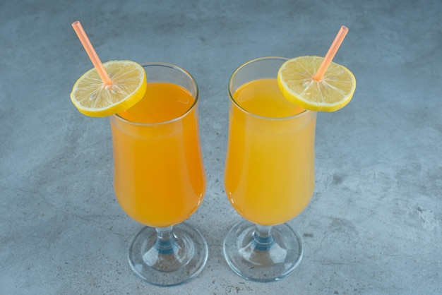 Dois sucos de frutas frescas em copos de vidro com canudos.