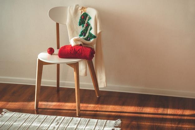 Dois suéteres de natal de inverno colocados em uma cadeira
