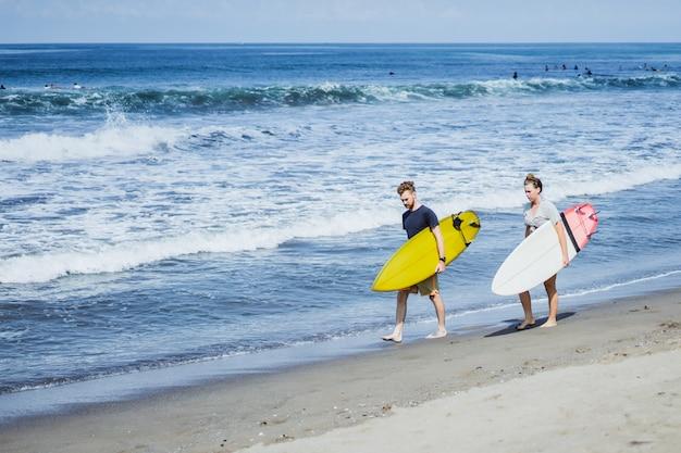 Dois surfistas caminhando à beira-mar