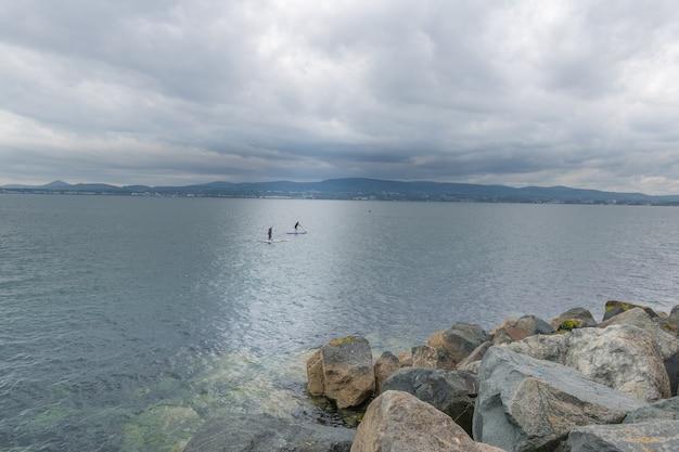 Dois surfistas estão nadando em uma prancha nas águas da baía de dublin.