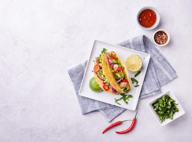 Dois tacos de rua mexicanos com frango, cebola, pimenta, milho e feijão em um prato branco com uma rodela de limão e especiarias. vista superior e espaço de cópia