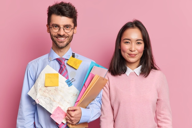 Dois talentosos estudantes do sexo feminino e masculino ficam contentes um ao lado do outro preparando um projeto científico