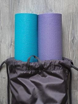 Dois tapetes para yoga, fitness ou pilates. mats em uma mochila cinza