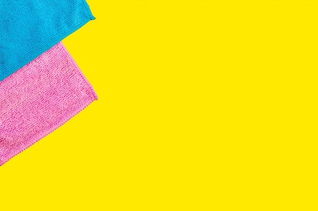 Dois tecidos em pó de microfibra encontram-se sobre um fundo amarelo brilhante