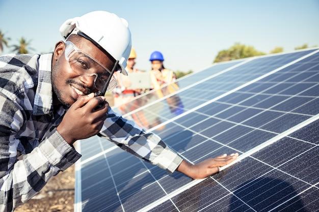 Dois técnicos de trabalhadores instalando pesados painéis solares solares na plataforma de aço alta no campo de milho