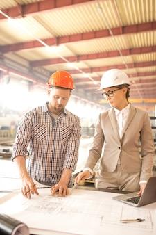 Dois técnicos profissionais em capacetes e roupas casuais discutindo detalhes do esboço e fazendo correções na reunião