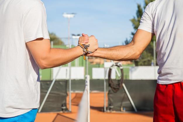 Dois tenistas profissionais, segurando as mãos sobre a rede de tênis antes da partida.