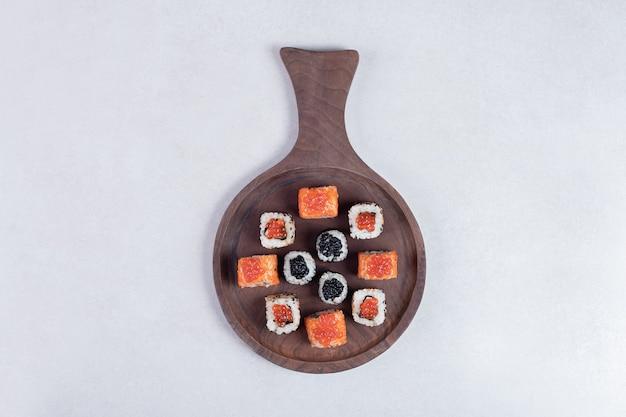 Dois tipos clássicos de sushi na placa de madeira com pauzinhos.