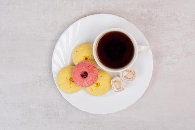 Dois tipos de biscoitos, delícias e xícara de chá na chapa branca.