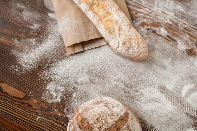Dois tipos de centeio caseiro fresco e pão de trigo e farinha na mesa de madeira