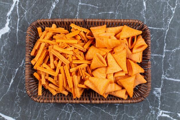 Dois tipos de chips crocantes na cesta de madeira.