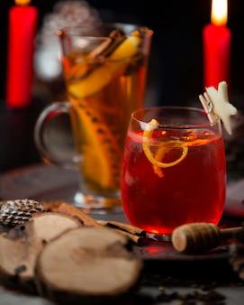 Dois tipos de cocktails vermelhos e amarelos na luz de velas vermelhas.
