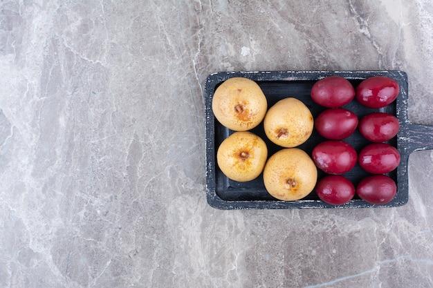 Dois tipos de frutas em conserva no quadro escuro.