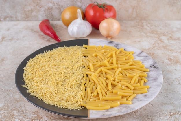 Dois tipos de macarrão cru em um lindo prato