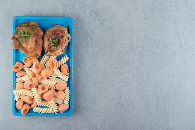 Dois tipos de macarrão e frango grelhado na placa azul.