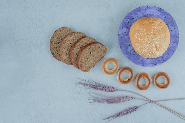 Dois tipos de pão e biscoitos na superfície da pedra
