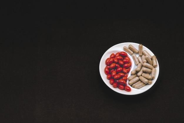Dois tipos de pílulas em uma mesa preta