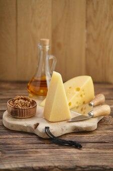 Dois tipos de queijos - parmesão e gouda com nozes e mel na placa de madeira com facas de queijo