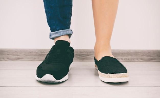 Dois tipos diferentes de sapatos nos pés da mulher