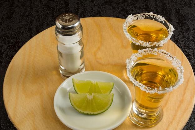 Dois tiros de tequila ouro na placa de madeira redonda