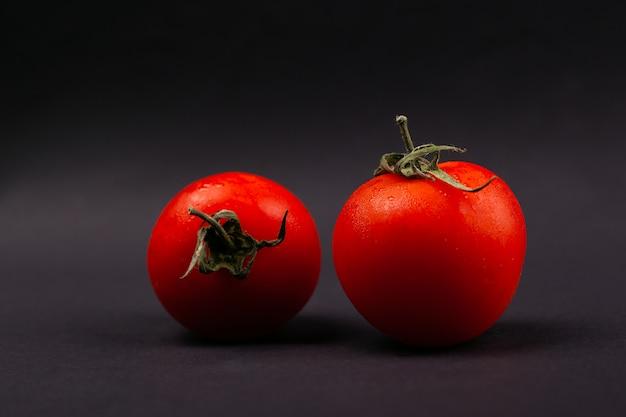 Dois tomates de cereja vermelhos em um fundo cinzento escuro.