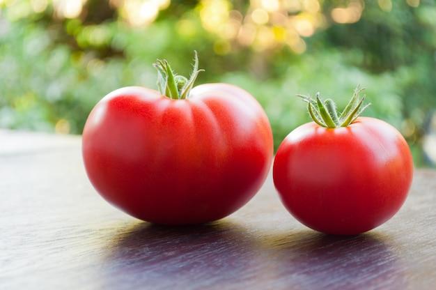 Dois tomates vermelhos frescos em uma mesa de madeira.
