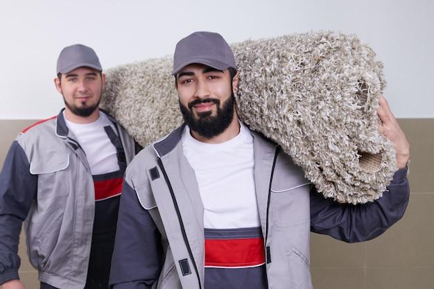 Dois trabalhadores carregando grande tapete após o serviço de limpeza