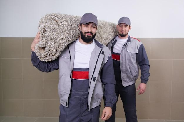 Dois trabalhadores carregando tapete grande após o serviço de lavagem