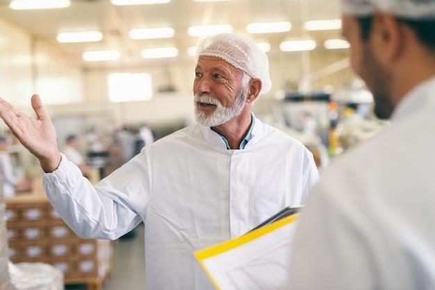 Dois trabalhadores caucasianos em traje de proteção, conversando e sorrindo em pé na fábrica de alimentos.