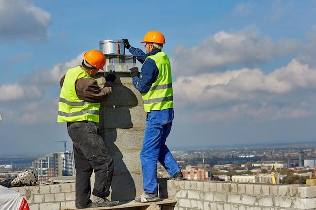 Dois trabalhadores com roupas de proteção e capacetes de segurança estão instalando um tubo para sistema de ventilação no telhado de um edifício moderno em construção