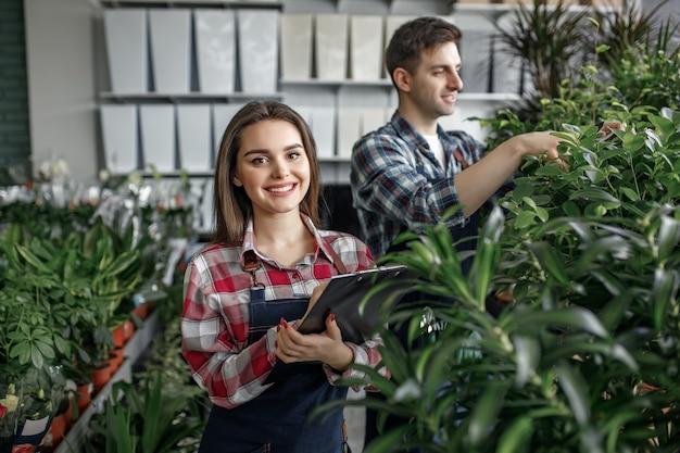 Dois trabalhadores com roupas especiais trabalhando no centro de jardinagem