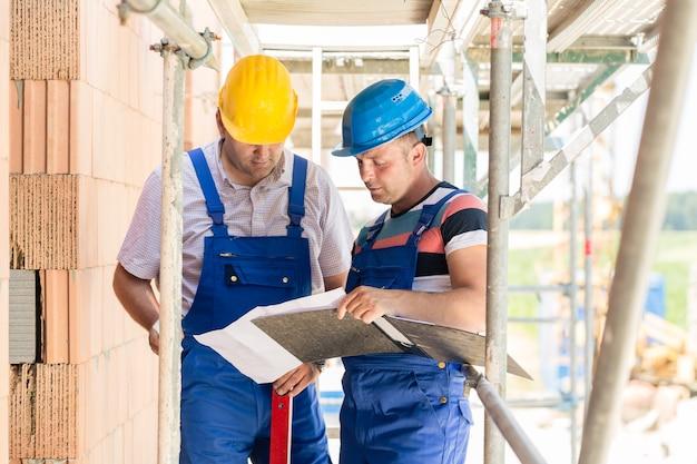 Dois trabalhadores da construção civil no local com capacetes discutindo no andaime com plantas
