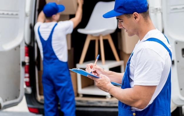 Dois trabalhadores da empresa de mudanças descarregando caixas do microônibus para a nova casa