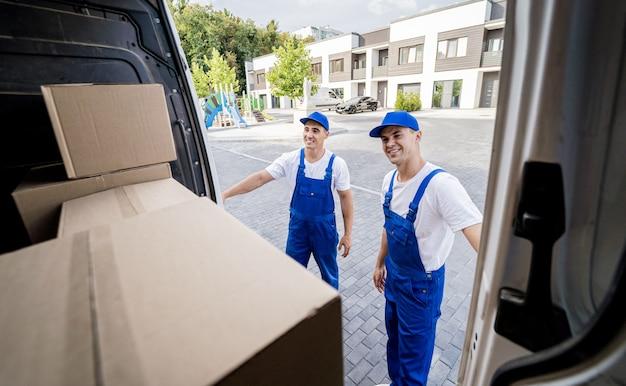 Dois trabalhadores da empresa de mudanças descarregando caixas do microônibus