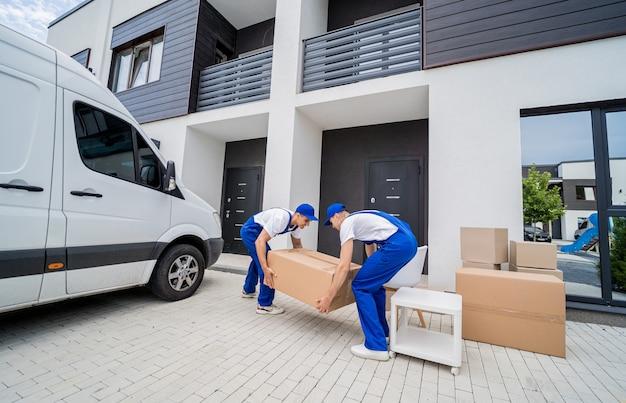 Dois trabalhadores da empresa de mudanças descarregando caixas e móveis do microônibus