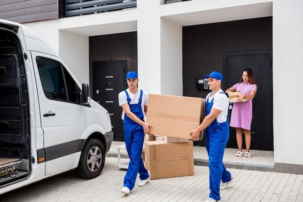 Dois trabalhadores da empresa de mudanças estão carregando as caixas em um microônibus