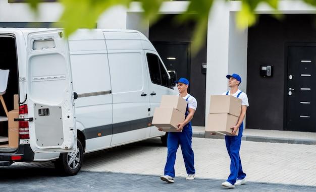 Dois trabalhadores da empresa de mudanças estão carregando caixas e móveis em um microônibus