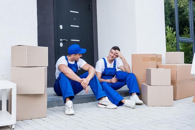 Dois trabalhadores da empresa de mudanças fazem uma pausa enquanto estão sentados no degrau