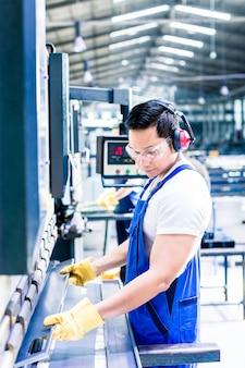 Dois trabalhadores da indústria inspecionando a peça de trabalho em pé no chão da fábrica com protetores auriculares e óculos de proteção