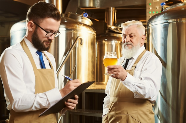 Dois trabalhadores de cervejaria examinando cerveja artesanal