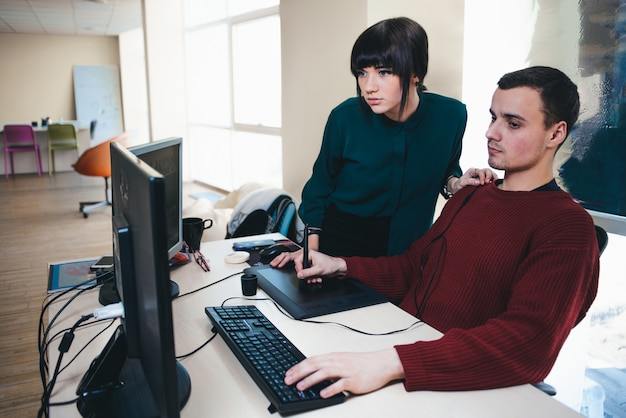 Dois trabalhadores de escritório jovem bonita olhando para um monitor de computador e discutir o projeto. a situação no escritório.
