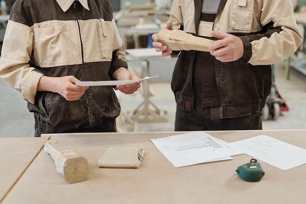 Dois trabalhadores de fábrica de móveis uniformizados em pé ao lado da bancada com desenhos e peças de madeira na reunião