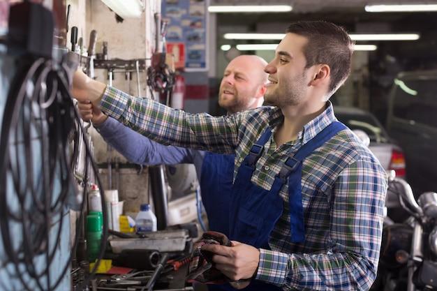 Dois trabalhadores de garagem perto de instalações