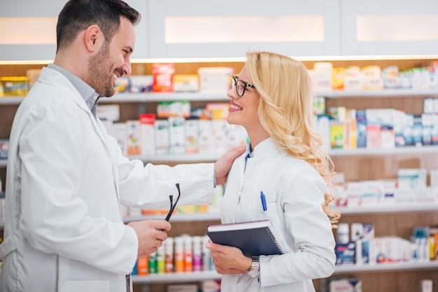 Dois trabalhadores de saúde sorrindo, olhando um ao outro na farmácia moderna.