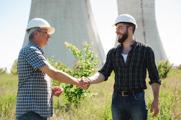 Dois trabalhadores de torre de linha de energia com aperto de mão.